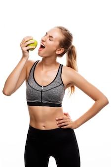 Linda mulher esportiva posando, segurando a maçã