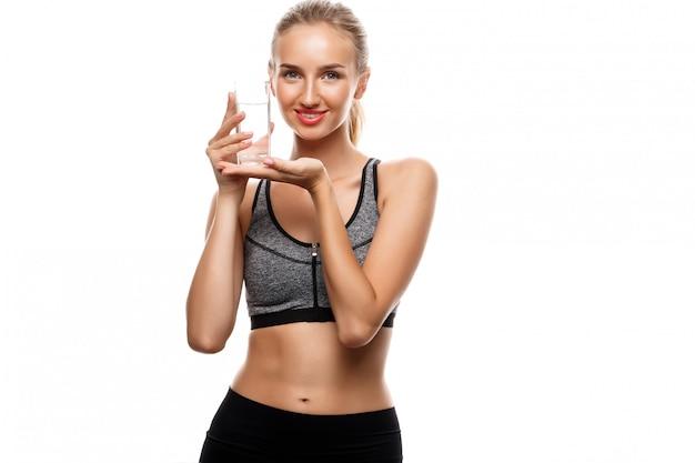 Linda mulher esportiva posando, segurando o copo de água