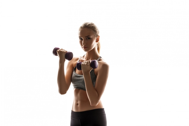 Linda mulher esportiva treinando com halteres