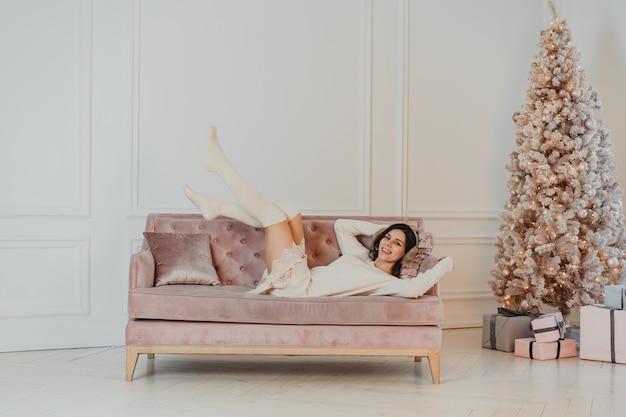 Linda mulher está deitada no sofá.