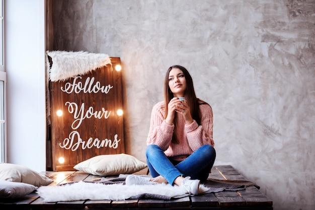 Linda mulher está sentada ao lado de lâmpada com letras siga seus sonhos. mulher inspirada está desfrutando de sua xícara de café.
