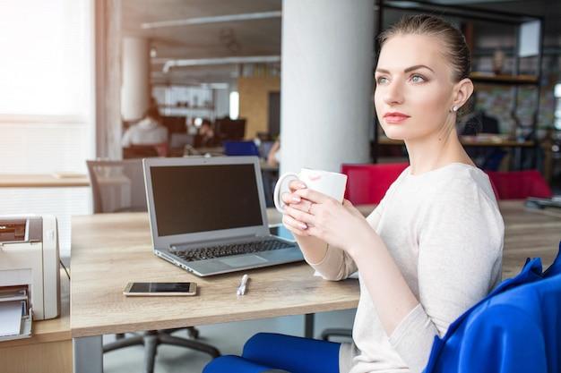 Linda mulher está sentada na cadeira e segurando uma xícara de chá