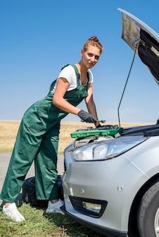 Linda mulher europeia conserta o carro na estrada