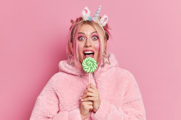 Linda mulher européia usa maquiagem lambe deliciosos doces que surpreendentemente aparecem na câmera e usa um casaco da moda e uma faixa de unicórnio na cabeça