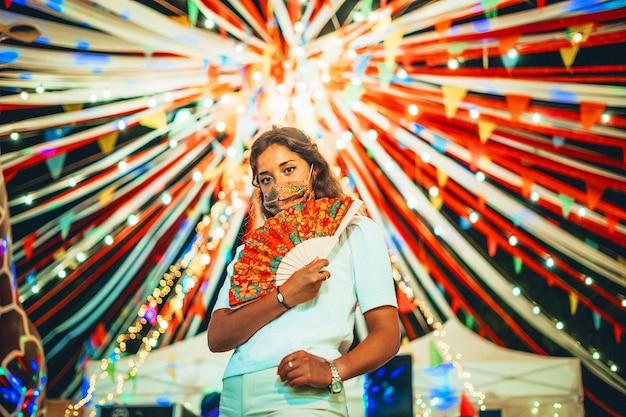 Linda mulher europeia usando uma máscara floral em um parque de diversões