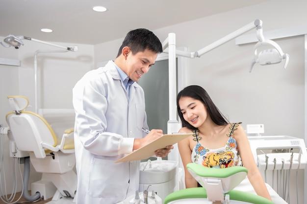 Linda mulher fala com dentista na clínica odontológica