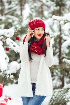 Linda mulher falando em um telefone móvel e segurando os presentes de natal.