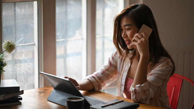 Linda mulher falando no celular enquanto estiver usando um tablet computador e sentado na mesa de trabalho de madeira, confortável sala de estar