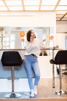 Linda mulher falando no telefone em pé na cozinha panorâmica com paredes brilhantes, mesa alta e cadeiras de bar