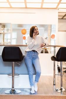 Linda mulher falando no telefone em pé na cozinha panorâmica, com paredes brilhantes mesa alta e cadeiras de bar