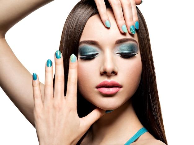 Linda mulher fashion com maquiagem turquesa e unhas - na parede branca