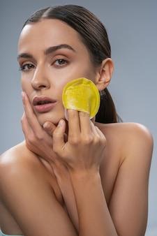 Linda mulher fazendo limpeza de rosto com pano