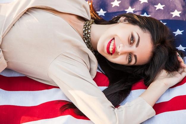 Linda mulher feliz com a bandeira americana, comemorando o dia da independência.