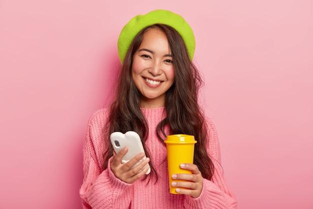 Linda mulher feliz com expressão alegre, usa celular para navegar nas redes sociais e bater papo online, segura xícara amarela para viagem com café