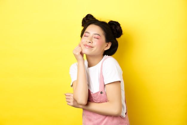 Linda mulher feliz com maquiagem rosa brilhante, feche os olhos e toque a pele macia, sorrindo animado, em pé com roupas de verão em amarelo.
