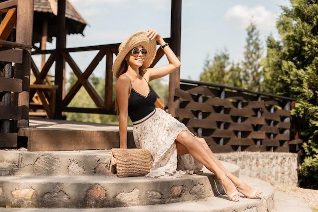 Linda mulher feliz com pernas sensuais com óculos de sol vintage em um chapéu de palha trançado, saia da moda e camisa de renda preta com sapatos senta-se nos degraus e descanse nas férias ensolaradas de verão