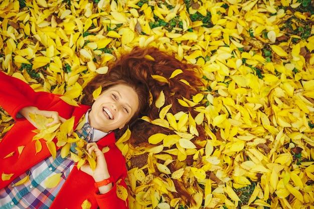 Linda mulher feliz deitado no outono amarelo folhas.