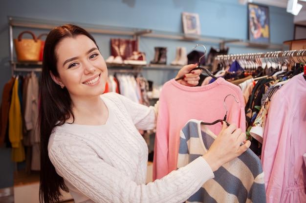 Linda mulher feliz desfrutando de compras na loja de roupas