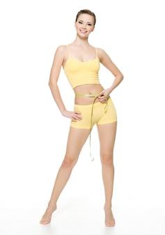 Linda mulher feliz desportiva medindo a cintura com tipo de medição isolado no branco. retrato de corpo inteiro.