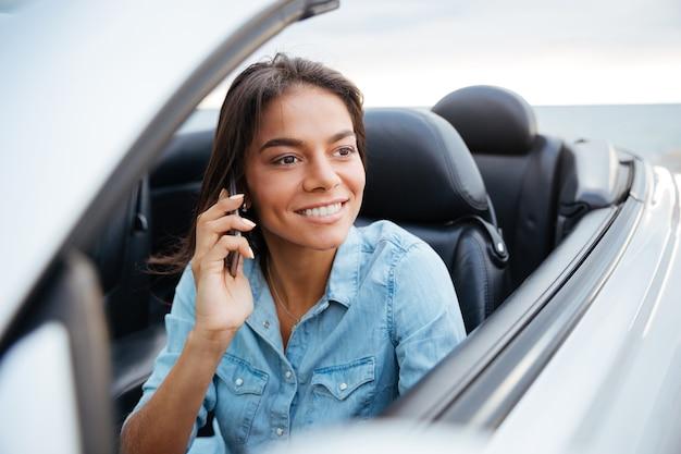 Linda mulher feliz dirigindo um carro e falando no celular