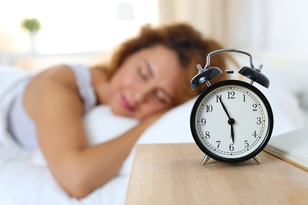 Linda mulher feliz dormindo no quarto dela pela manhã. conceito de bem estar e sono saudável.