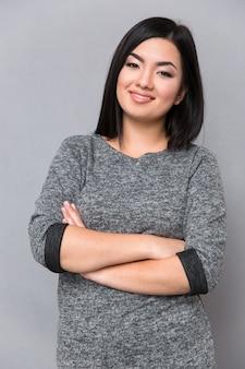 Linda mulher feliz e sorridente asiática em um macacão cinza olhando para a frente com os braços cruzados