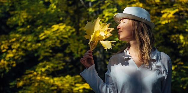 Linda mulher feliz e sorridente com um buquê de folhas de bordo amarelas no rosto