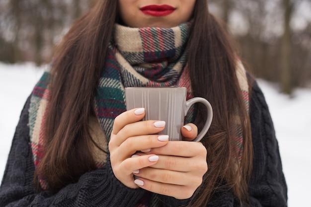 Linda mulher feliz e sorridente com uma xícara no inverno na rua