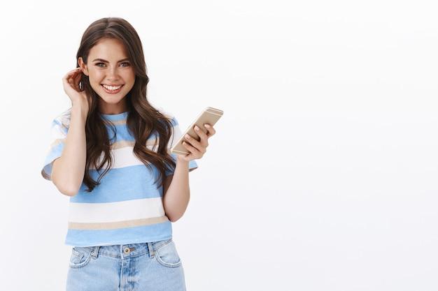 Linda mulher feliz e sorridente usando smartphone, coloque uma mecha de cabelo atrás da orelha, boba, olhe para a frente, divertida e alegre, rindo de felicidade, fazendo uma ligação, use o aplicativo móvel