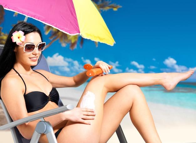 Linda mulher feliz em biquíni preto aplicando protetor solar creme no corpo bronzeado.