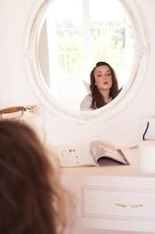 Linda mulher feliz em seu quarto perto de sua penteadeira, posando antes da festa - camarim rosa