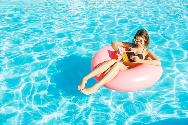 Linda mulher feliz lendo um livro com anel inflável relaxante na piscina azul