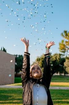 Linda mulher feliz na festa de confraternização com confetes caindo por toda parte nela