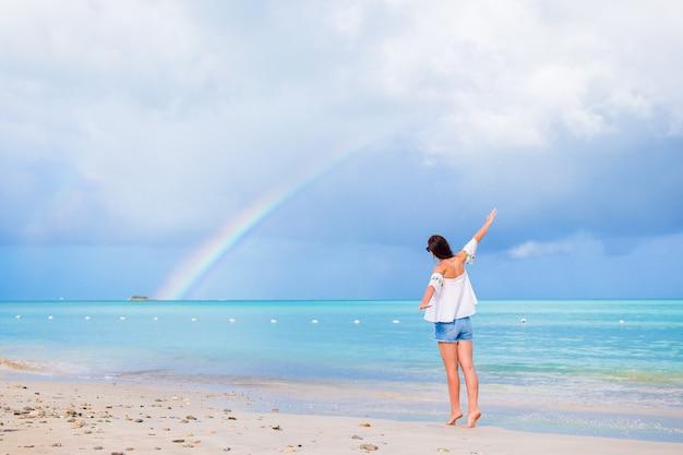Linda mulher feliz na praia com um lindo arco-íris sobre o mar