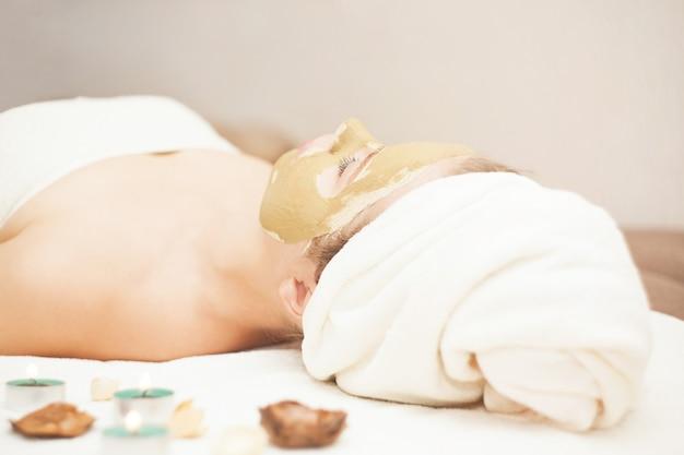 Linda mulher feliz no spa fazendo tratamento de máscara facial. foco seletivo