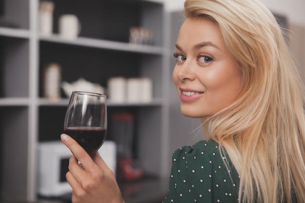 Linda mulher feliz relaxando em casa tomando um copo de vinho