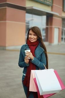 Linda mulher feliz segurando sacolas de compras e café para viagem