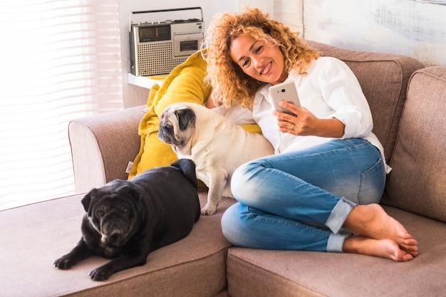 Linda mulher feliz sentada no sofá tirando uma selfie com seus dois pugs fofos, adorável cachorro doméstico
