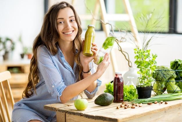 Linda mulher feliz sentado com bebidas e alimentos verdes saudáveis em casa. conceito de refeição vegana e desintoxicação