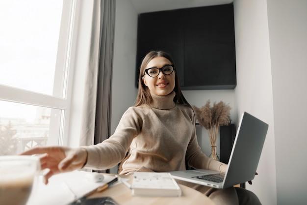 Linda mulher feliz trabalhando em casa com o laptop tomando café. mulher de negócios sorridente usando óculos no escritório, usando um laptop