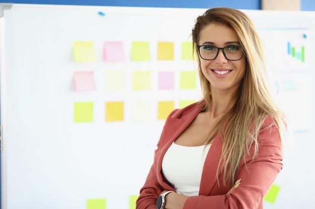 Linda mulher ficar no quadro branco de fundo com adesivos coloridos.