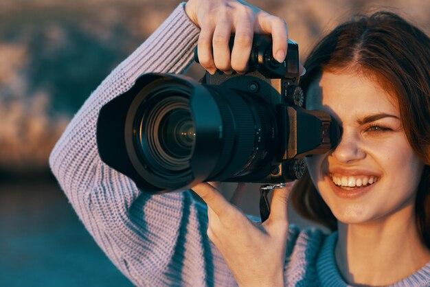 Linda mulher fotógrafa na natureza nas montanhas fotografa o modelo da paisagem