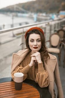 Linda mulher francesa bebe café usando uma caneca de café sentada no terraço do restaurante com uma caneca de café