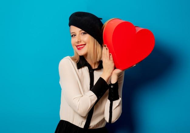 Linda mulher francesa em boina com caixa de presente em forma de coração
