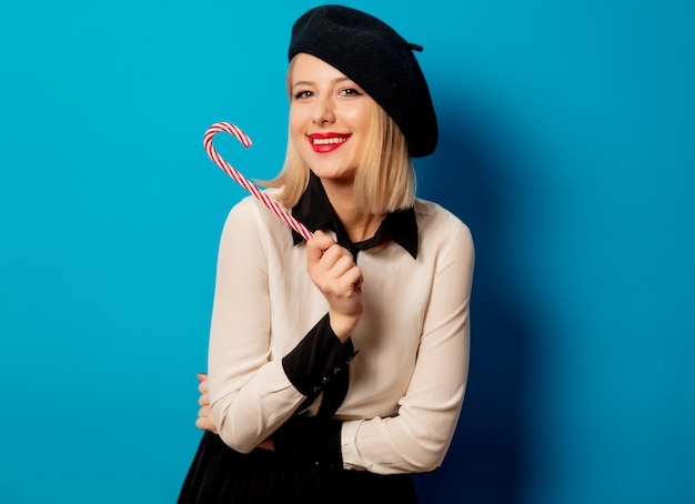 Linda mulher francesa em boina com pirulito doce na parede azul