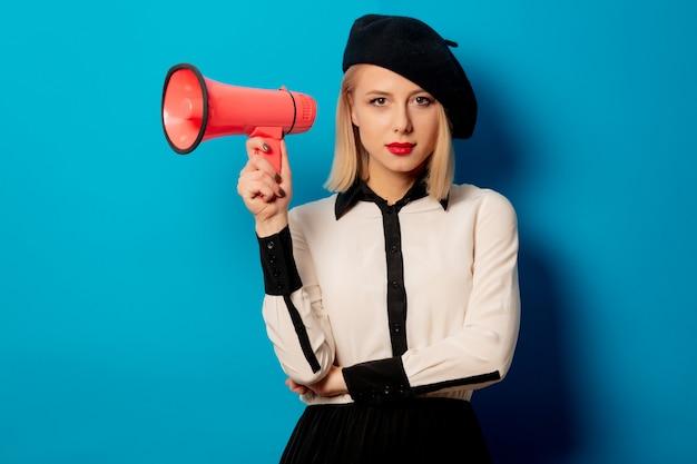 Linda mulher francesa em boina detém alto-falante na parede azul