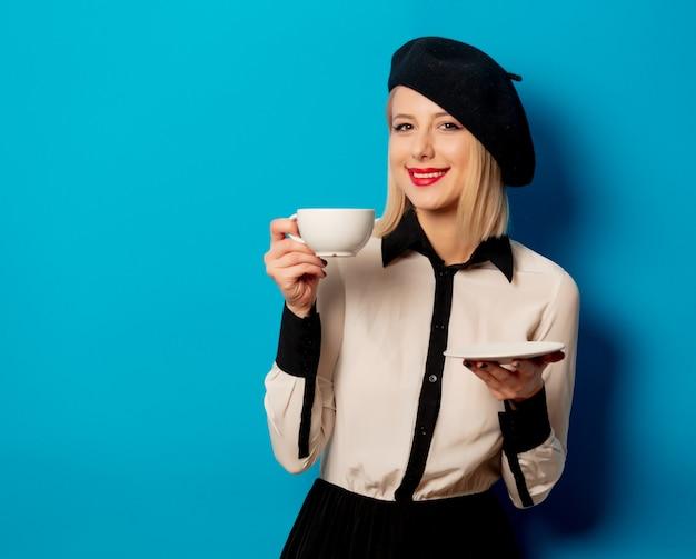 Linda mulher francesa em boina detém branca xícara de café