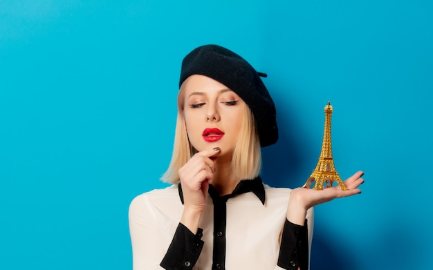 Linda mulher francesa em boina detém miniatura torre eiffel