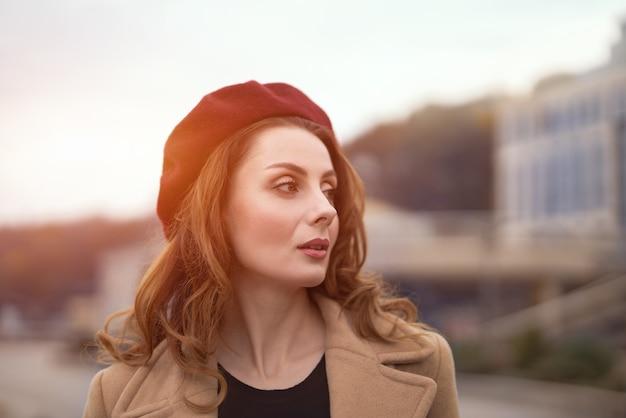 Linda mulher francesa encantadora com um casaco bege outonal e boina vermelha ao ar livre com a cidade urbana