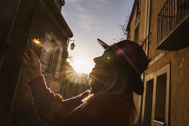 Linda mulher francesa segurando uma vara de brilho sendo acender com um isqueiro